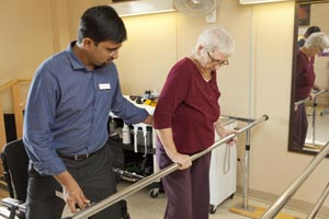 healthcare professional assisting elderly woman with walking