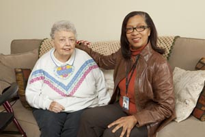 Care Coordinator sitting with elderly woman on sofa