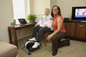 elderly woman using exercise equipment with Care Coordinator by her side
