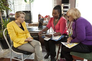 Care Coordinator speaking with femal patient and with female caregiver