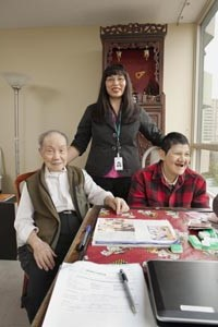 Care Coordinator with two individuals who are playing a board game
