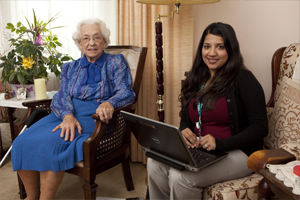 female Care Coordinator holding laptop sitting beside elderly woman