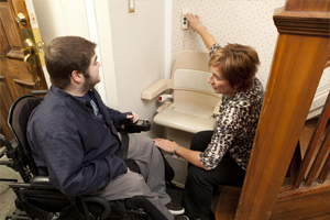 Care Coordinator showing patient show to use chair lift