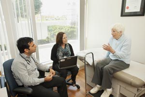 Two health care providers listen to a patient