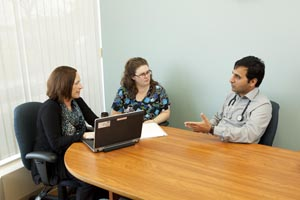 Health care providers discuss during a meeting