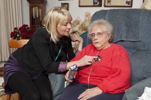 A health care provider listens to a patient's heart with a stethoscope