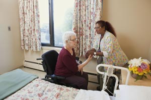 A health care provider helps a client to stand up
