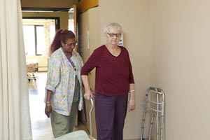 A health care provider helps a client to use a cane