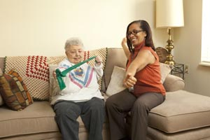 A health care provider shows a patient how to use a stretchy arm band