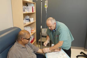 A health care provider inserts an IV into a patient's arm