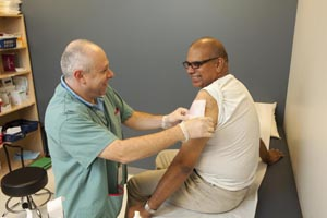 A health care provider puts a bandage on a man's arm