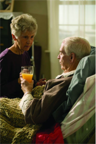 A woman gives orange juice to a man in bed