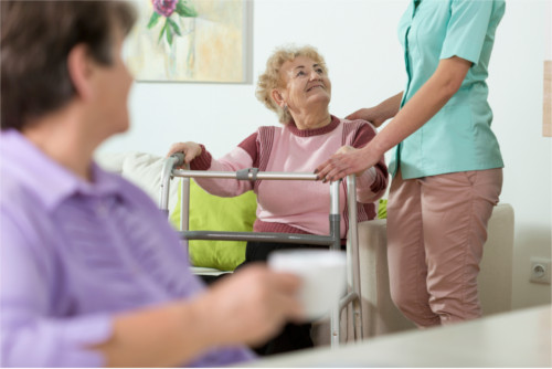 young helpful nurse and older woman with walker