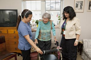 senior female using a wlaker with assistance of personal support worker and care coordinator