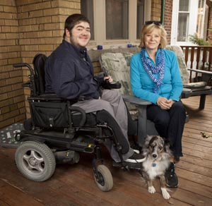 Patient sitting with caregiver and dog on front porch of his home
