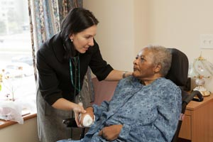 A care provider speaks with a patient in a long-term care home